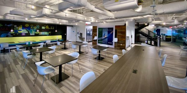 Open concept office dining area with exposed white duct work ceiling