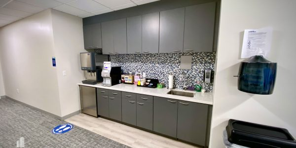 Custom gray storage cabinets and counter with tile backsplash in bank office in Norfolk Dominion Tower