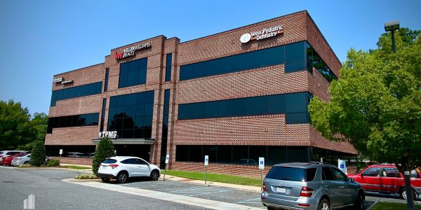 Front right exterior of three-story corporate brick building on Volvo Parkway in Chesapeake