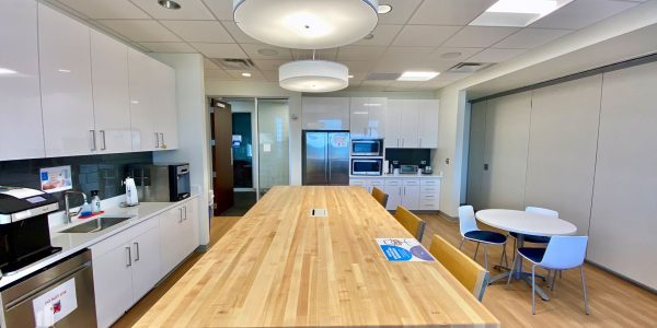 Spacious high rise office break room with dishwasher, fridge, sink, microwave, and seating