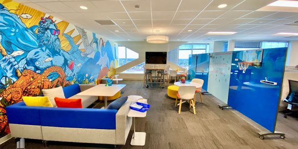 Office lounging area with colorful seating options and vibrant mural on wall