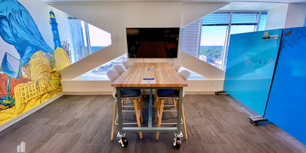 Office lounge with table and TV nearby floor to ceiling windows