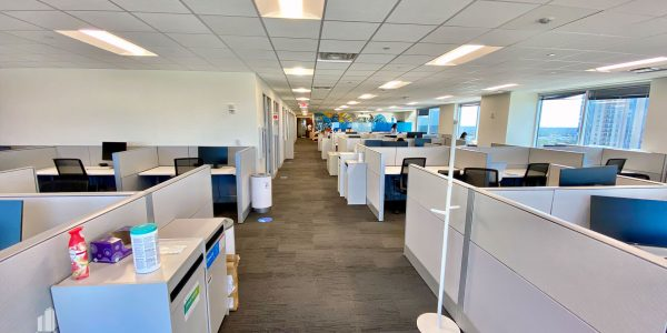 Cubicle Workspace in large open room with floor to ceiling windows