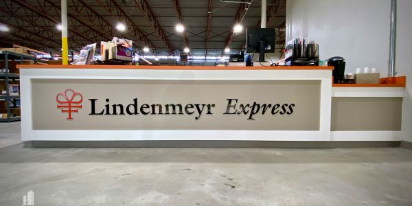 front view of an orange, white, and tan receptionist desk at Lindenmeyr Munroe warehouse